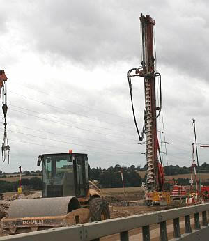 A drill to place foundations down through the soil into the firm ground below. Motorway carriageway widening, M1, Bedfordshire.